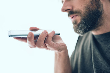 close-up of bearded caucasian man recording voice message or using voice assistant on mobile phone