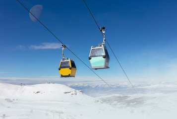 In the Spanish winter sports area Pradollano high in the Sierra Nevada. Cable car cabins in front of blue sky and snowdrifts in the air.