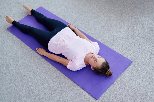 Young woman lying on yoga mat with eyes closed in savasana pose at home. Fitness, sport and healthy lifestyle concept. Corpse pose
