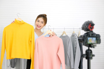 Youn asian woman fashion blogger showing cloth with smiling face while recording new content for vlog and fashion online shopping with camera at home studio