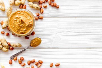 Product for hearty breakfast with peanut butter in bowl near nuts on white wooden background top view mockup