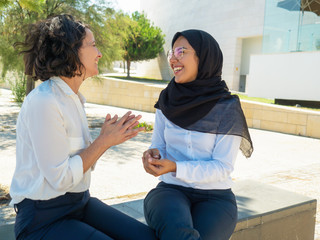 Joyful multiethnic friends and colleagues discussing good news outside. Women in office suits and hijab sitting outdoors, chatting and laughing. Friendly colleagues concept