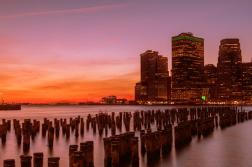 Wall Mural - View from the water of the bay on the night city center of New York at sunset. Skyscrapers glowing in the dark against the sunset sky.