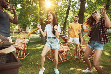 Group of happy friends having beer and barbecue party at sunny day. Resting together outdoor in a...