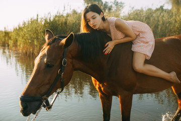 Woman lies astride a horse at river. Fototapete