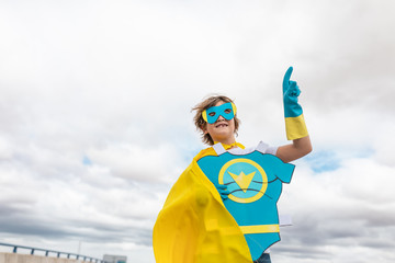 Wall Mural - cheerful boy and smiling in superhero costume