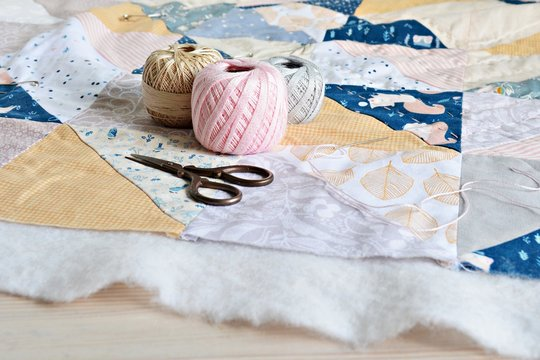 Hand stitch quilting process: cotton thread, needle and scissors on the table