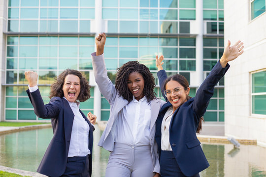 Happy excited businesswomen rejoicing at corporate success. Team of women wearing office suits, making winner gestures, smiling and shouting for joy. Business leadership concept