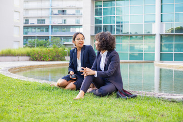 Barefoot businesswomen sitting on grass. Young multiethnic businesswomen in formal wear sitting together on lawn and talking. Coworkers concept