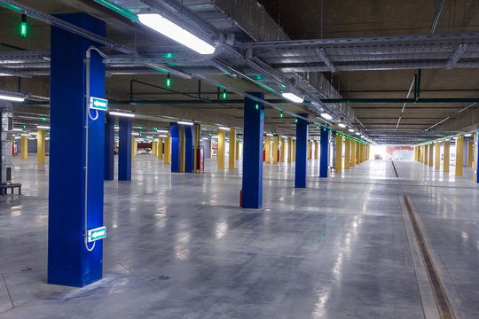 car parking inside the building, columns with lighting and LED directions
