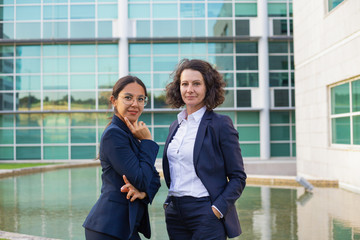Confident female business professionals posing outside. Two women wearing office suits, standing near office building and looking at camera. Successful businesswomen concept