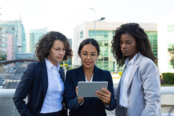 Concentrated businesswomen with digital tablet. Focused multiethnic female colleagues standing and using tablet pc together on street. Technology concept