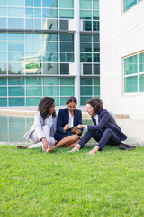 Businesswomen with smartphone resting on lawn. Full length view of multiethnic female colleagues sitting on green grass and using smartphone. Technology concept