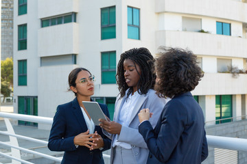 Professional businesswomen with tablet computer. Multiethnic female colleagues in formal wear standing together and using digital tablet outdoor. Technology concept