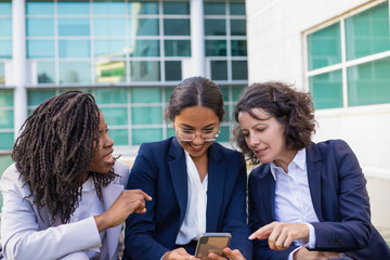 Happy businesswomen with smartphone outdoor. Cheerful multiethnic female colleagues sitting together and using cell phone outdoor. Technology concept