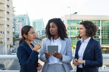 Professional businesswomen with tablet pc. Multiethnic female colleagues in formal wear standing together and using digital tablet outdoor. Technology concept