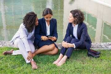 Barefoot businesswomen with smartphone outdoor. High angle view of multiethnic female colleagues sitting on green lawn and using mobile phone. Technology concept