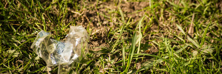 Background with crumpled transparent plastic wrap in the grass