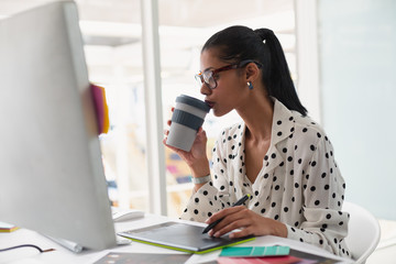 Female Graphic designer having coffee while using graphic tablet at desk