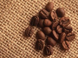 Whole grains of black coffee on burlap