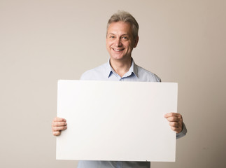 Happy mature man with blank advertising board