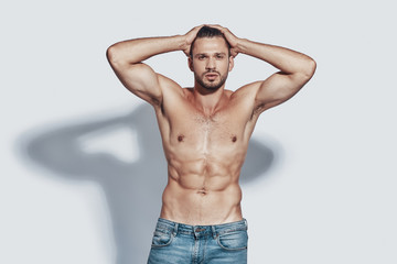 Handsome young shirtless man looking at camera and keeping head in hands while standing against grey background