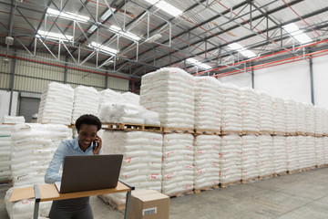 Female manager talking on mobile phone while using laptop at desk in warehouse