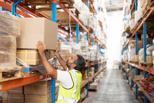 Male worker putting cardboard box on a rack in warehouse