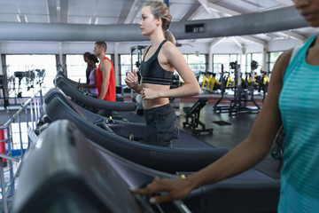 Woman exercising on treadmill in fitness center