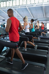 Fit people exercising on treadmill in fitness center