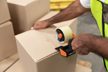 Male worker packing cardboard box with tape gun dispenser in warehouse