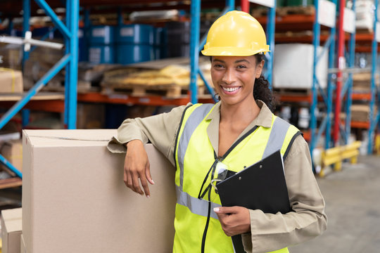 Female staff smiling while standing in warehouse