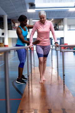 Female physiotherapist helping disabled senior woman walk with parallel bars in sports center