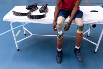 Man removing his prosthetic leg in sports center