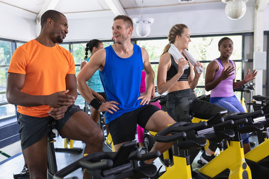Fit people interacting with each other exercising on exercise bike in fitness center
