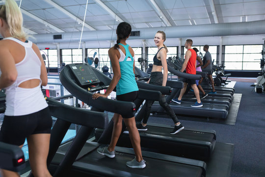 Fit woman interacting with her female friend while exercising on treadmill