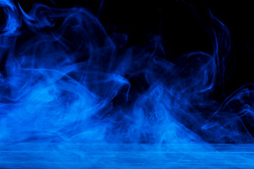 Conceptual image of blue smoke isolated on dark black background and wooden table.