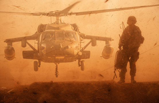 Military soldier walking at desert in front of helicopter in sand storm.