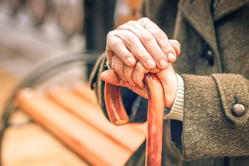 Close up of hands of elderly man leaning on cane