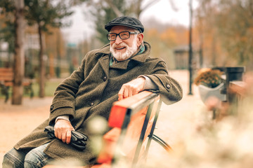 Elegant senior man sitting on bench in park