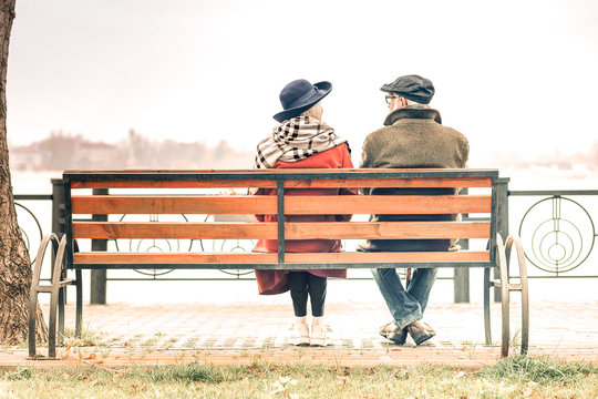 Back view of a senior couple sitting on bench in autumnal park