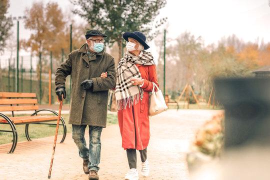 Stylish senior couple wearing face masks walking in park together
