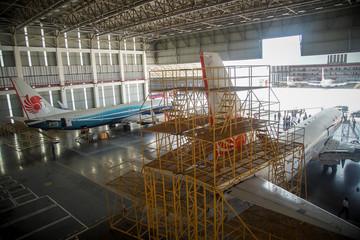 Workers check Lion Air's airplanes during a routine maintenance at Batam Aero Technic (BAT) facilities at Hang Nadim International airport in Batam island