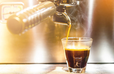 Barista making a espresso with a classic coffee machine.