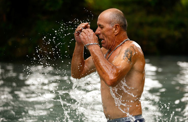 Man dips in cold waters of Golubaya Krinitsa, (Blue Spring) during celebration of Orthodox Honey Savior, which is also called the Savior on Water, near the town of Slavgorod