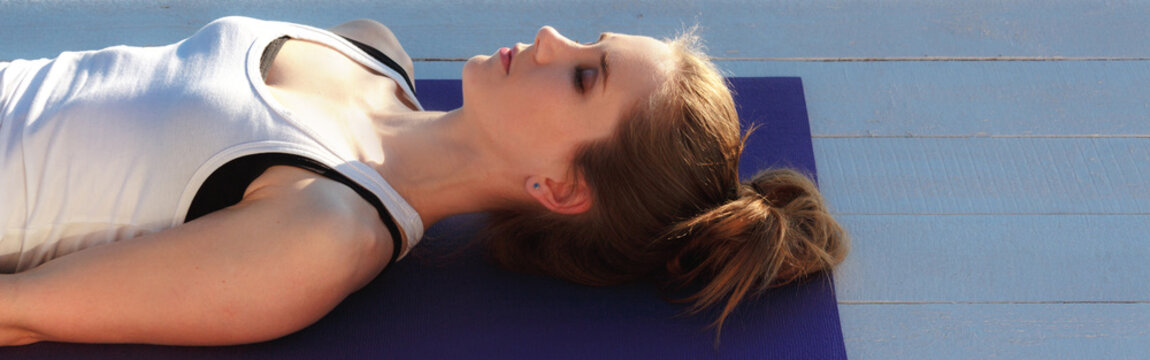 Young woman practicing yoga outdoors. Girl in shavasana on purple mat on white wooden floor. Portrait in profile close up.