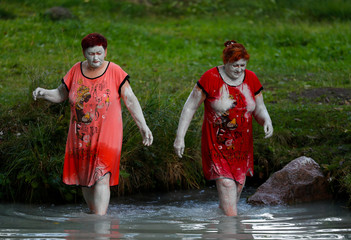 Women with their faces covered with clay walk in waters of Golubaya Krinitsa, (Blue Spring) during celebration of Orthodox Honey Savior, which is also called the Savior on Water, near the town of Slavgorod