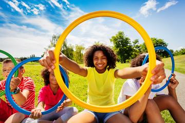 Girl in group of kids look through colorful hoop