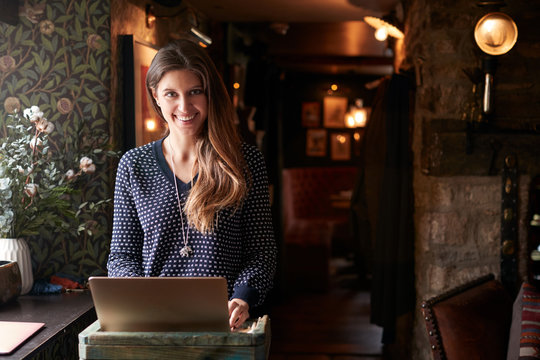 Portrait Of Female Receptionist Working On Laptop At Hotel Check In
