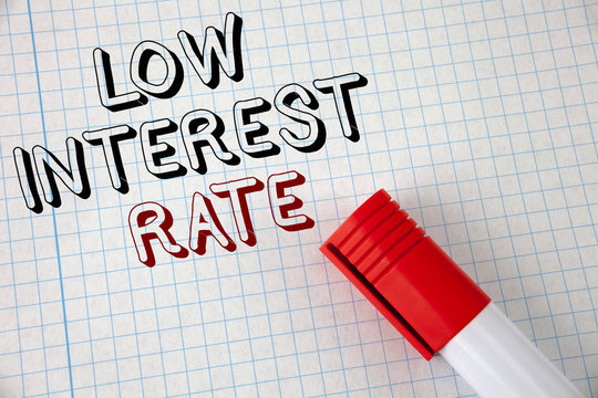 Handwriting text Low Interest Rate. Concept meaning Manage money wisely pay lesser rates save higher written Notebook Paper Marker next to it. Top view.